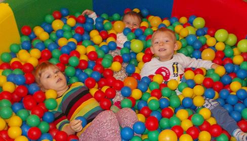 zdjęcie trójki dzieci zatopionych w kolorowych kulkach