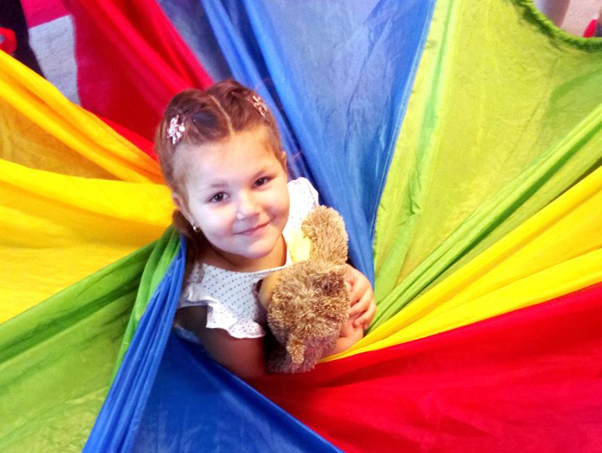 zdjęcie uśmiechniętej dziewczynki wplecionej w kolorowe husty