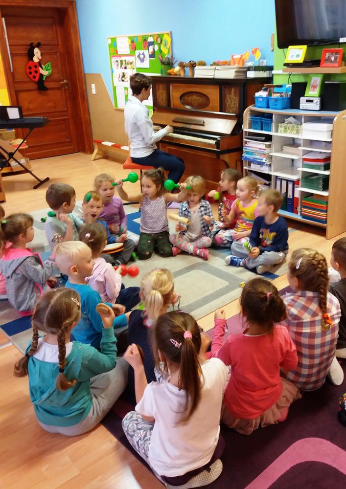 zdjęcie zajęć muzycznych, dzieci siedzą w kółku a pani gra na pianinie