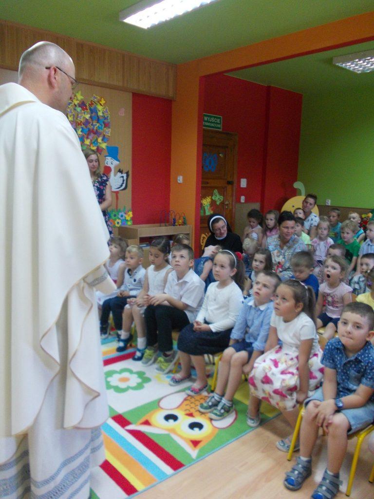 dzieci słuchają księdza