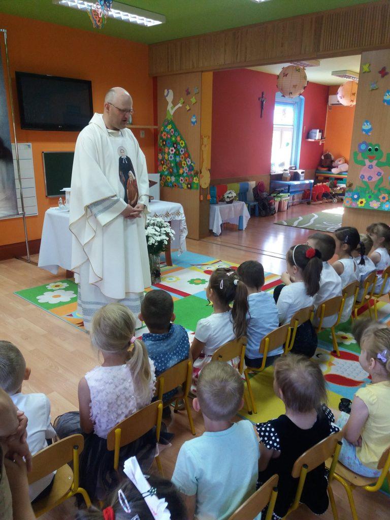 ksiądz rozmawia z dziećmi