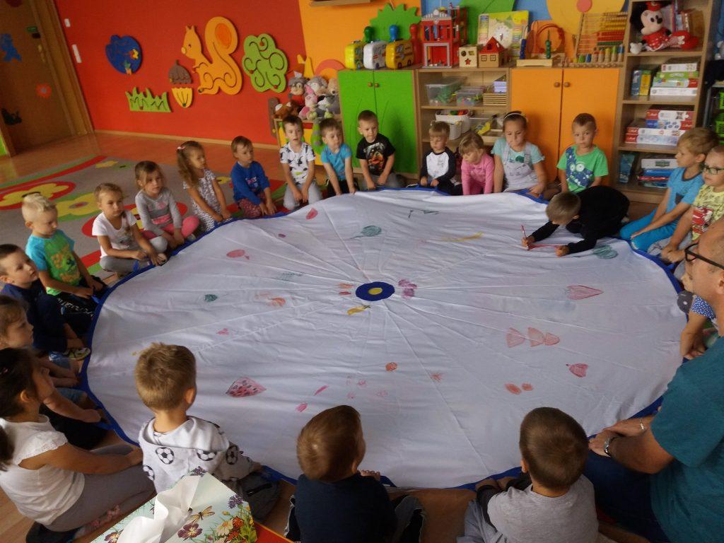 dzieci siedzą wokół chusty