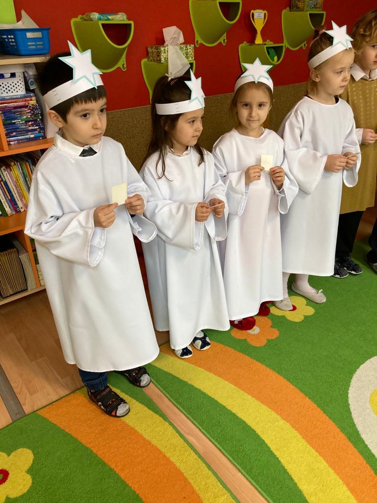 czworo dzieci w białych szatach z opłatkami