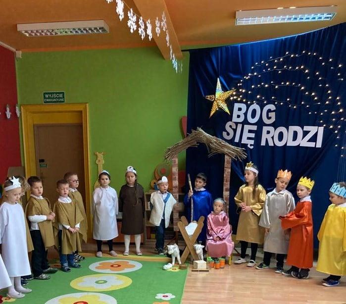 grupa dzieci w strojach śpiewa kolędy